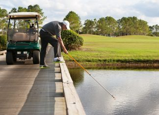 retreiving golf ball from water hazard Getty Images/iStockphoto