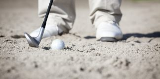 Macro of golfer in bunker. Getty Images/iStockphoto
