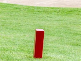 The red distance marker pole to inform range of golfing with blurred green golf course. Getty Images/iStockphoto