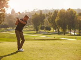 Male Golfer Lining Up Tee Shot On Golf Course Monkey Business Images