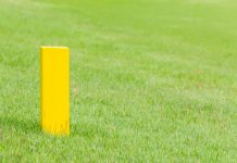 The yellow distance marker pole to inform range of golfing in green golf course. Getty Images/iStockphoto