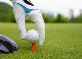 Hand putting golf ball on tee in golf course Getty Images/iStockphoto