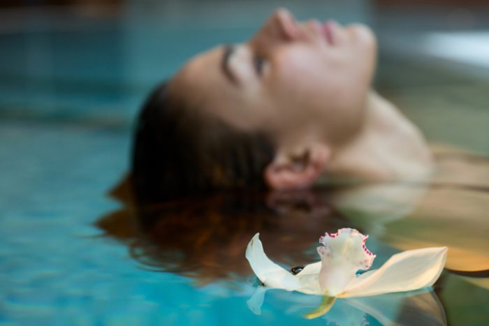 Europe. Italy. Helvetia Thermal SPA Hotel Porretta Terme. model swimming in thermal pool with an orchid floating Universal Images Group via Getty