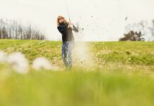 Close-up of field with woman playing golf in background at golf course Lisa Lindqvist Liljedahl
